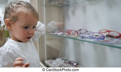 Little child -blonde girl in ophthalmology clinic chooses...