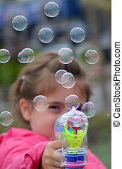 Little child blowing soap bubbles with a bubbles gun