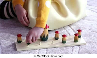 Little Child collects a children's wooden toy mushrooms,...