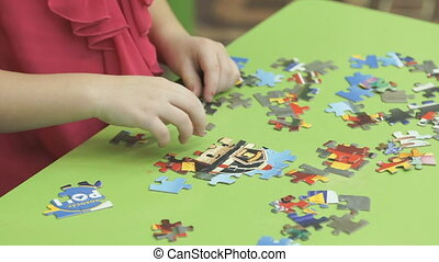 Little child collects picture from puzzles
