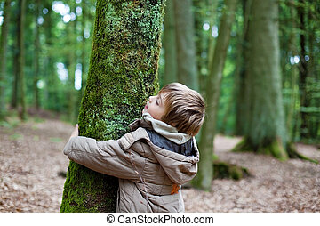 Little child embracing tree trunk