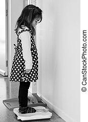Little child examining weight - Little child , girl age 4 , ...