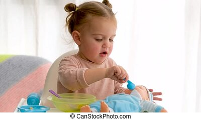 Adorable baby girl feeding and playing with lying toy doll