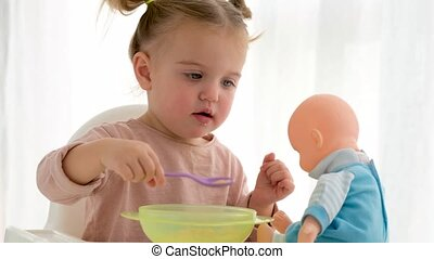 Adorable baby girl feeding and playing with toy doll