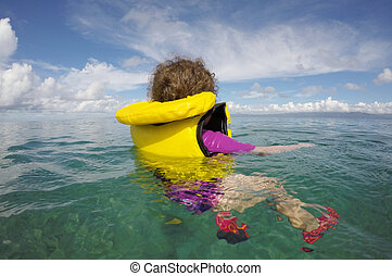 Little child floating with a life jacket alone in the ocean