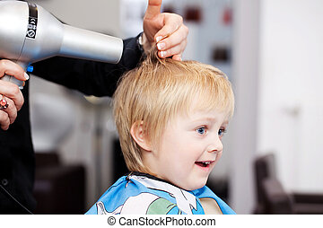 Little child getting a blow dry at the hairdresser - Little...