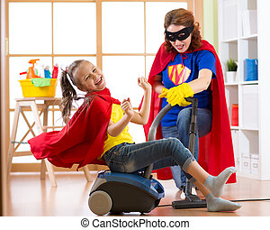 Little child girl and her mother play while doing cleanup at home