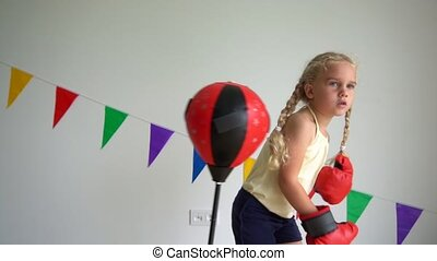 little child girl box with gloves on punching bag. Gimbal stabilizer movement slow motion shot