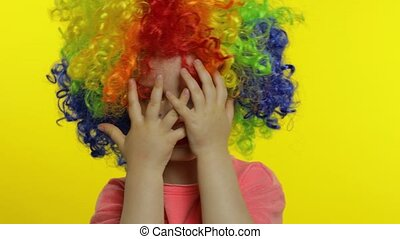 Little child girl clown in colorful wig hides behind her ...
