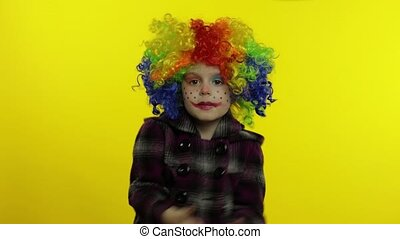 Little child girl clown in colorful wig making silly faces, having fun, smiling, dancing. Halloween