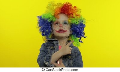 Little child girl clown in colorful wig making silly faces. Having fun, smiling, dancing. Halloween