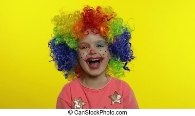 Little child girl clown in colorful wig making silly faces. Having fun, smiling, laughing. Halloween