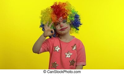 Little child girl clown in colorful wig making silly faces. ...