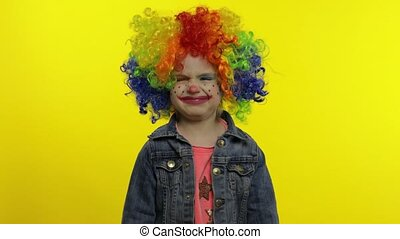 Little child girl clown in colorful wig receives money ...