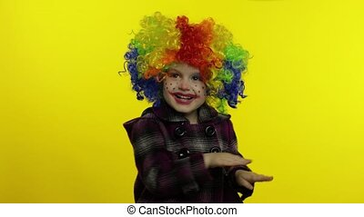 Little child girl clown in rainbow wig making silly faces. Having fun, smiling, dancing. Halloween