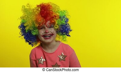 Little child girl clown in rainbow wig making silly faces. Having fun, smiling, laughing. Halloween