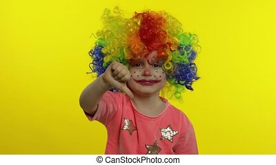 Little Child girl clown in rainbow wig making silly faces. Having fun, smiling. Thumb up. Halloween