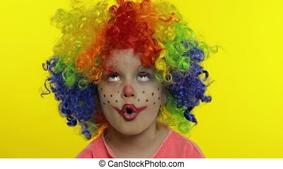 Little Child girl clown in wig making silly faces. Fool around, singing, showing tongue. Halloween