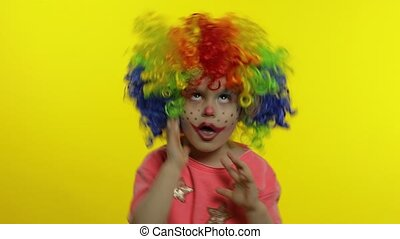 Little Child girl clown in wig making silly faces. Having fun, smiling, showing tongue. Halloween