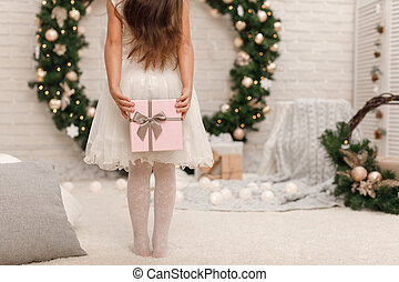little child girl holding present box. Back view.