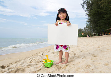 Little child girl holds a white board at beach