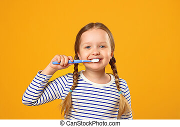 Little child girl in striped pajamas brushing her teeth with a toothbrush. The concept of daily hygiene. Yellow background.