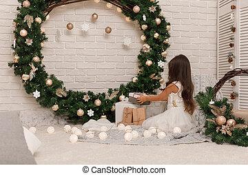 little child girl in white dress holding present christmas box.