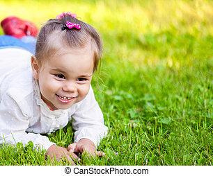 Little child girl lying on field