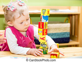 Little child girl playing with toy letter and number blocks ...