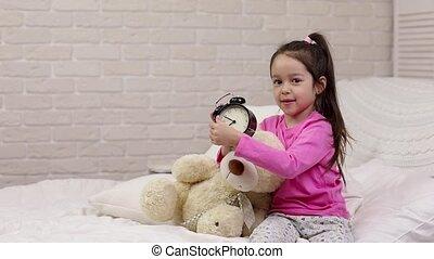 little child girl sets the alarm in bed - little child girl...