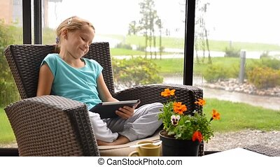 Little child girl sitting on the terrace in armchair with digital tablet