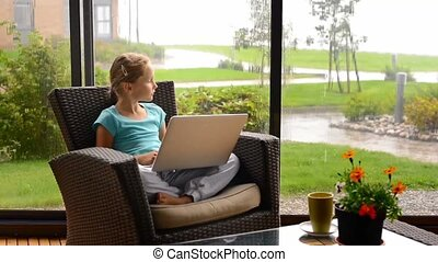 Little child girl sitting on the terrace in armchair with laptop