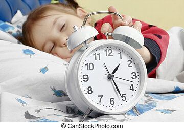 little child girl sleeping in bed with alarm clock