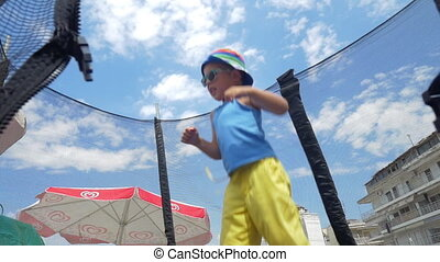 Little child having fun on tramp outdoor - PEREA, GREECE -...