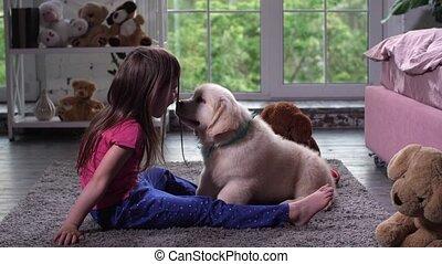Little child having fun with puppy pet on carpet - Joyful...