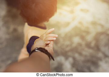 Little child holding her father is hand