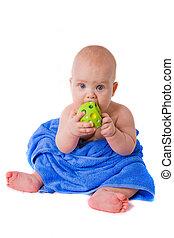little child in a blue towel biting green ball