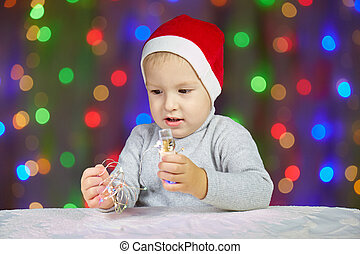 Little child in a Santa Claus hat on the background of garlands