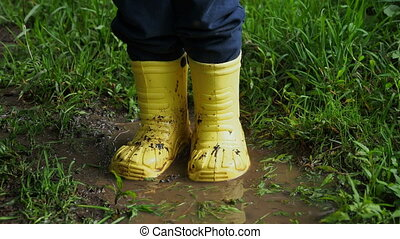Little child in bright yellow rubber boots splashing in a...