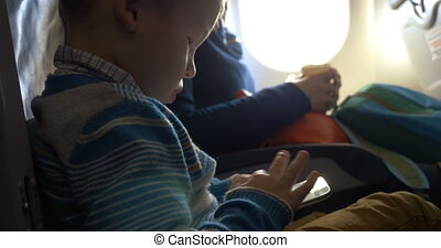 Little child in plane using smartphone