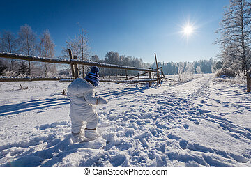 Little child in snow field. Little child boy walking in winter field