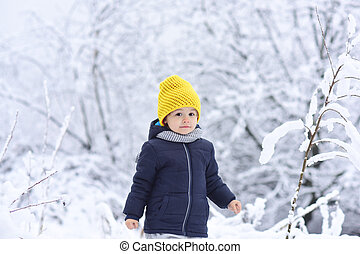 Little child in winter forest. Young boy walking in winter snowy park alone. Winter vacation with children. Cute boy spending wintertime outside. Blue jacket and yellow hat, hipster in the forest