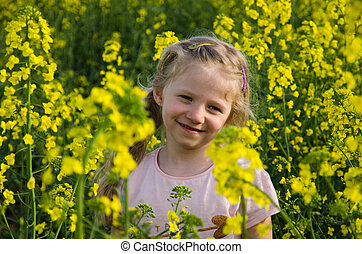 little child in yellow rapeseed field