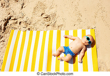 Little child infant lay on beach mat from above