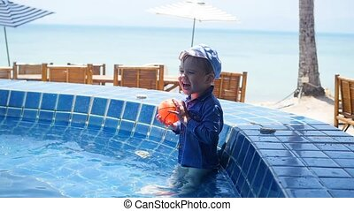 Little child is playing ball in the pool. Sports in the open air.