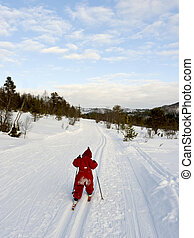 Little child long distance cross country skiing alone in a winter landscape.