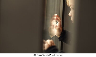 Little child looking out of the window and reflecting in it