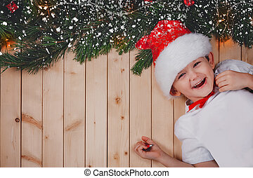 Little child lying on floor with fir tree branch. Holiday concepts