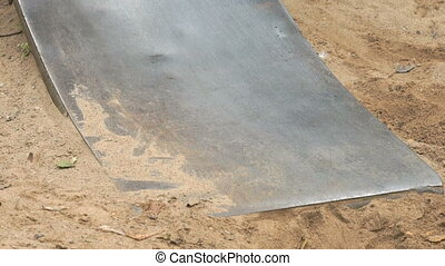 Little child moving down on a steel slide outdoors