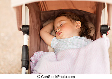 little child or baby sleeping in stroller outdoors